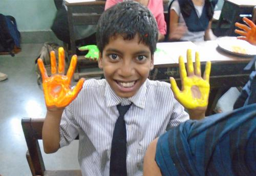 mentee-excitedly-holds-up-his-coloured-hands-main